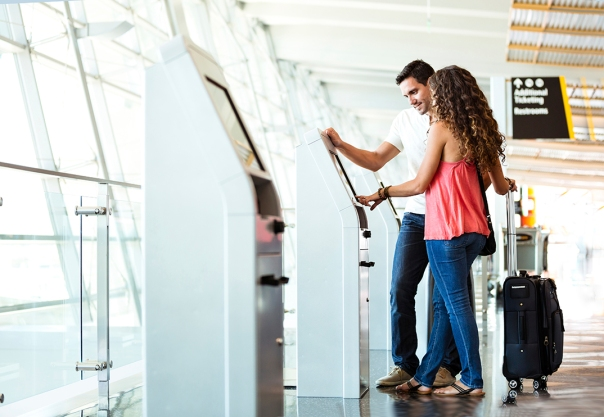 Couple using automated check-in machine at airport