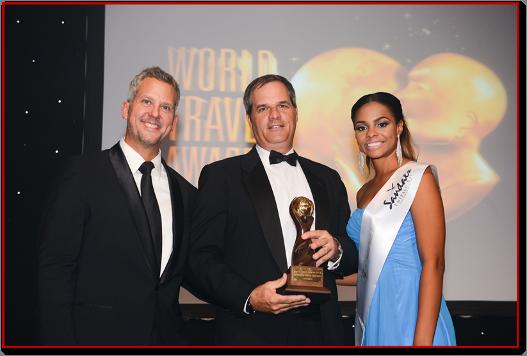 Acima: William Tatham (no centro), Vice Presidente da Cruise Shipping & Marina Operations, autoridade portuária da Jamaica recebendo o prêmio de Melhor Destino do Caribe ao lado do apresentador Andrew Kennedy (esquerda).