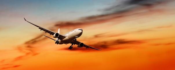 jet airplane landing at sunset, panoramic frame